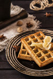 Ginger waffles with honey. Ginger waffles topped with honey and decorated with candied ginger with anise and nutmeg on a dark wooden background Royalty Free Stock Images