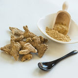 Ginger roots and powder. Ginger on white with spoon and bowl in background royalty free stock images