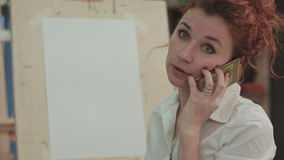 Ginger woman artist talking on the phone next to the easel stock video footage