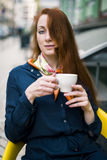 Ginger woman with coffee cup. Royalty Free Stock Photography