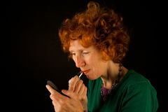 Ginger woman colouring her lips Stock Images