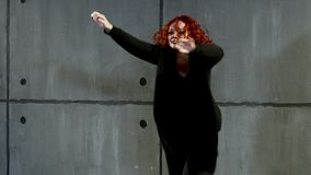 Ginger woman doing hip-hop near by wall. Young red-haired woman performs in black clothes near wall stock footage