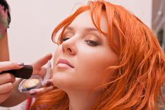 Ginger woman having make-up applied Stock Photos