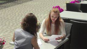 Ginger woman inspects document`s material with colleague in outdoor cafe. Shooting from the back of brunette girl. Two beautiful young women sitting in outdoor stock video