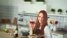 Ginger Woman Reading Culinary Book dans la cuisine Fille rousse banque de vidéos