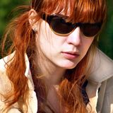 Ginger woman in sunglasses. Portrait of woman with ginger hair and sunglasses or shades outdoors; green nature background stock image