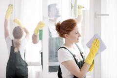 Woman cleaning window. A ginger women and her two coworkers in yellow gloves and green overalls cleaning windows royalty free stock photography