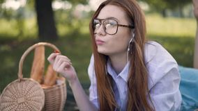 Ginger young girl lying on grass, eating strawberry and listening to music stock video footage
