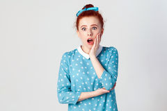 Ginger young girl screaming with shock, holding hands on her cheeks. Isolated studio shot on gray background.  Royalty Free Stock Image