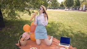 Ginger young woman singing using a baguette as a microphone in park stock footage