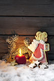 Gingerbread angel on pile of snow against wooden wall Stock Image