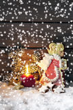 Gingerbread angel on pile of snow against wooden wall Royalty Free Stock Photo