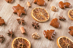 Gingerbread with baking ingredients like cinnamon, orange slices and star anise on wooden background, christmas background Stock Photos