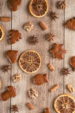 Gingerbread with baking ingredients like cinnamon, orange slices and star anise on wooden background, christmas background Stock Photography