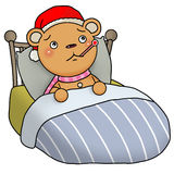 Gingerbread bear - sick. Gingerbread bear sick lying on bed and taking temperature with a thermometer Stock Photo