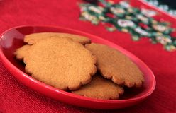 Gingerbread biscuits on christmas plate. Gingerbread biscuits on red plate and christmas tablecloth Stock Images