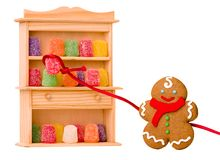 Gingerbread boy and gumdrops. Gingerbread boy taking gumdrops from a cabinet.  White background Royalty Free Stock Photos