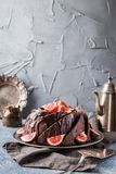 Gingerbread Bundt Cake. For Christmas with figs and lingonberry over gray background Royalty Free Stock Image