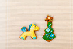 Gingerbread cake pony christmas tree with icing decoration on brown. Homemade gingerbread cake pony and christmas tree with icing and colorful decoration on stock photos