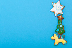 Gingerbread cake pony christmas tree star with icing decoration on blue. Homemade gingerbread cake pony christmas tree and star with icing and colorful royalty free stock photo
