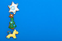 Gingerbread cake pony christmas tree star with icing decoration on blue Stock Photos