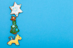 Gingerbread cake pony christmas tree star with icing decoration on blue. Homemade gingerbread cake pony christmas tree and star with icing and colorful royalty free stock images