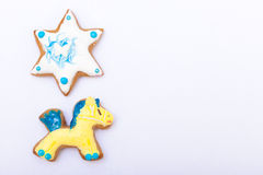 Gingerbread cake pony star with icing decoration on white. Homemade gingerbread cake pony and star with icing and colorful decoration on white as background stock photos