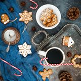 Gingerbread, candy cane and coffee cup on dark background. Christmas or New year composition. Flat lay. Top view Stock Images