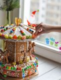 A gingerbread carousel and some Christmas decoration elements on a white wooden surface. A handmade gingerbread carousel and some Christmas decoration elements Stock Photo