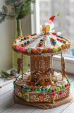 A gingerbread carousel and some Christmas decoration elements on a white wooden surface. A handmade gingerbread carousel and some Christmas decoration elements Stock Images