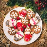 Christmas cookies with festive decoration. Plate with tasty New Year homemade sweets on wooden table. Royalty Free Stock Photo