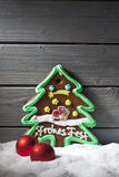 Gingerbread christmas tree christmas bulbs on heap of snow against wooden background Stock Images