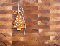 Gingerbread Christmas Tree Cookie. Hanging by twine over a wooden background Royalty Free Stock Photography