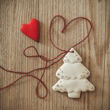 Gingerbread christmas tree hanging over wooden background with heart stock photography