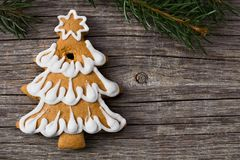 Gingerbread Christmas tree and spruce branches on a wooden backg. Round with copy space Stock Photo