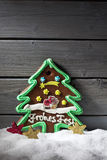 Gingerbread christmas tree star shaped decorations on heap of snow against wooden background Stock Photo