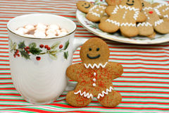 Gingerbread Cookie and Cocoa. A smiling gingerbread man stands next to a hot cup of cocoa with marshmallows.  Full plate of cookies in the background Stock Photo