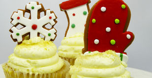 Gingerbread cookie cupcakes. Close-up of three golden cupcakes decorated with gingerbread cookies of a snowflake, mitten and stocking Stock Images