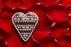 Gingerbread cookie in heart shape on a red rose petals backgroun Stock Photography