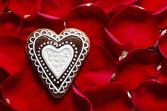 Gingerbread cookie in heart shape on a red rose petals backgroun Royalty Free Stock Images