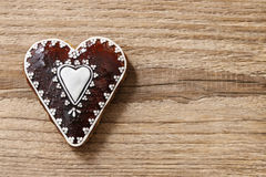 Gingerbread cookie in heart shape on a wooden background Stock Photos