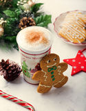 Gingerbread cookie man and hot cup of cappuccino. Traditional Christmas dessert. Copy space Stock Images