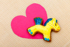Gingerbread cookie pony icing pink heart love. Homemade gingerbread cake pony with icing and blue yellow decoration and paper heart love symbol on brown paper stock photo