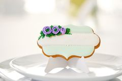 Gingerbread cookie sugared with glaze flowers and pearls. Cute gingerbread cookie sugared with blue and green glaze flowers and pearls stands on a white plate on stock photo