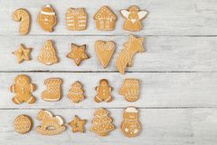 Gingerbread cookie world. Top view of different shapes of nicely decorated gingerbread Christmas cookies on white wooden background stock photos