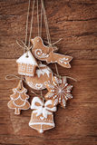 Gingerbread cookies. Hanging over wooden background Stock Photo