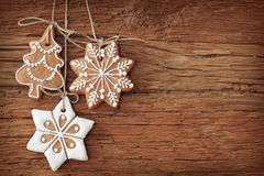 Gingerbread cookies. Hanging over wooden background Stock Images