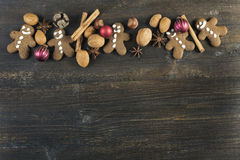Gingerbread cookies,  baubles, nuts and spices christmas background on wood Stock Photo