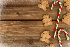Gingerbread cookies and candy canes in decoration on wooden table royalty free stock image