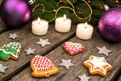 Gingerbread cookies and Christmas decoration over wooden table Royalty Free Stock Images